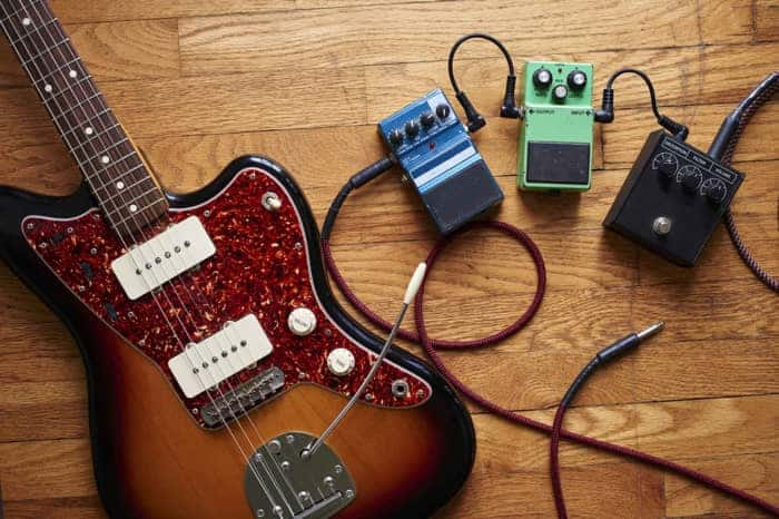 Why do new guitar strings sound tinny